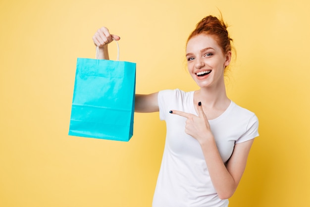 Happy ginger woman holding packet and pointing at him Free Photo