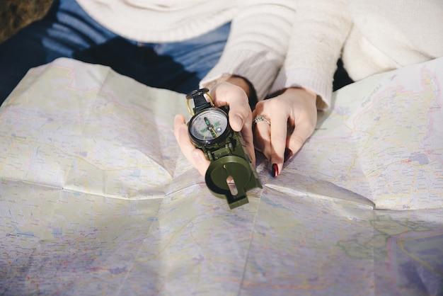 Счастливая девушка и парень с туристическим рюкзаком и гитарой, глядя на маршрут с компасом и картой, концепция истории любви, выборочный фокус Premium Фотографии
