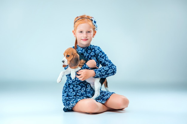 The happy girl and a beagle puppy on gray wall Free Photo