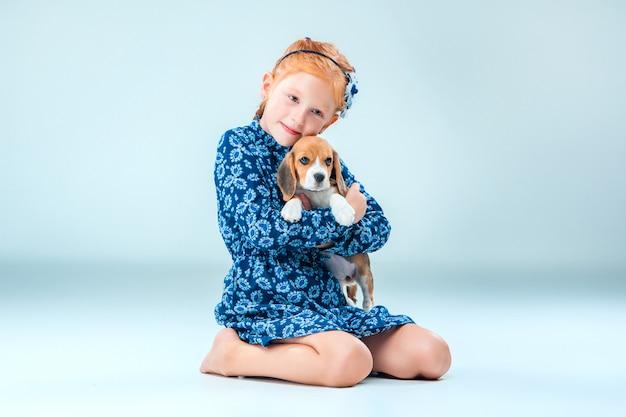 La ragazza felice e un cucciolo di beagle Foto Gratuite