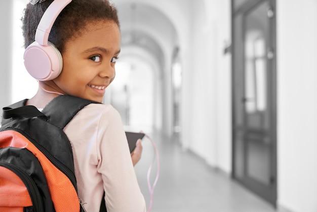 Happy girl in big pink headphones listening music Premium Photo