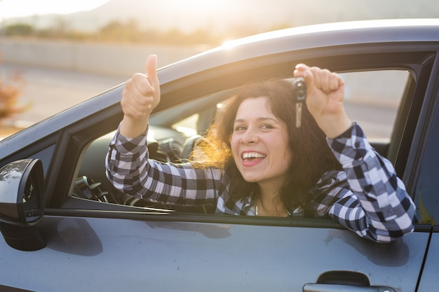 Happy girl in a car showing a key and thumb up gesture. Premium Photo