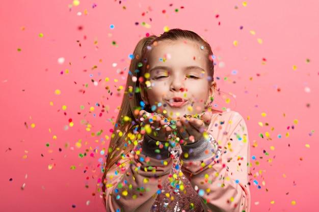 Happy girl celebrating on a pink background. Premium Photo
