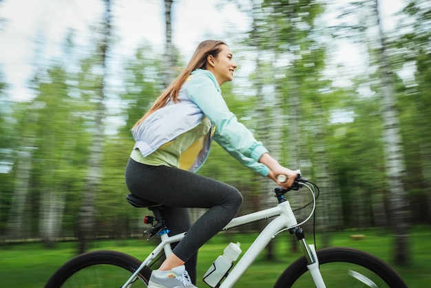 Happy girl cyclist riding on a mountain bike outside. adventure travel. Free Photo