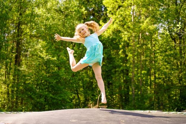 Una ragazza felice in un vestito salta su un trampolino in un parco in una soleggiata giornata estiva Foto Gratuite