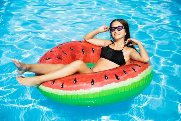 Happy girl floating in swimming pool Free Photo