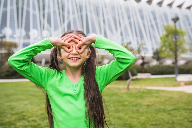 Happy girl forming goggle with her finger standing in park Free Photo