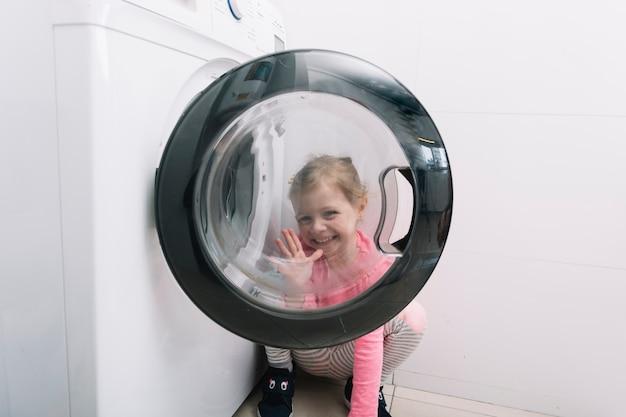 Happy girl gesturing through washing machine door Free Photo