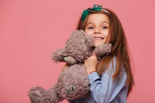 Happy girl having long auburn hair smiling playing with her lovely toy teddy bear Free Photo