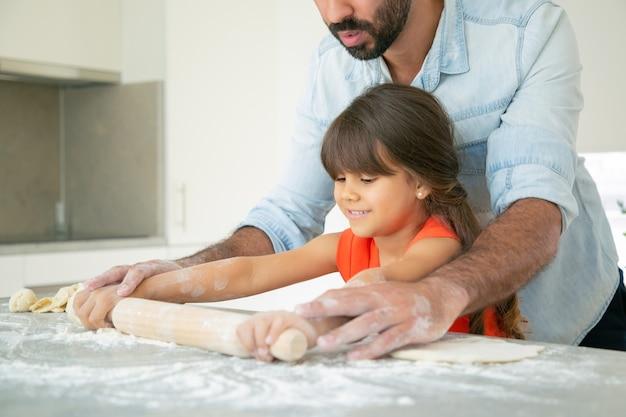 Ragazza felice e suo padre che rotolano la pasta sul tavolo della cucina con farina disordinata. Foto Gratuite