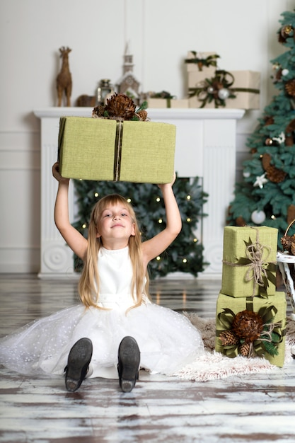Happy girl holding a big box with a gift over her head. winter holidays, christmas and people concept Premium Photo
