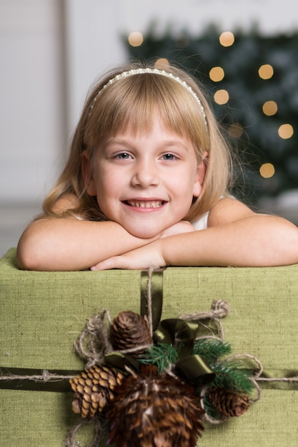 Happy girl holding a big box with a gift over her head. winter holidays, christmas and people concept. Premium Photo