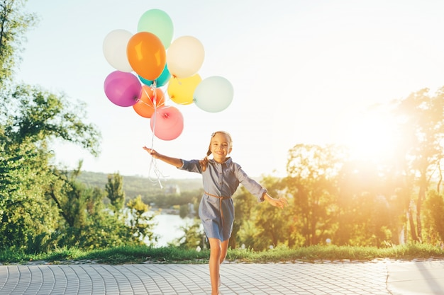 Happy girl holding colorful balloons in the city park Free Photo