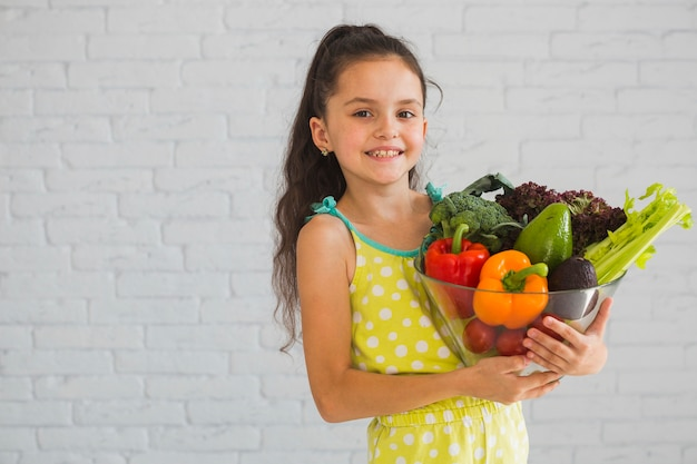 Happy girl holding colorful vegetable in glass bowl Free Photo