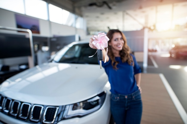 Ragazza felice che tiene le chiavi del suo suv nuovo di zecca presso lo showroom del concessionario auto Foto Gratuite