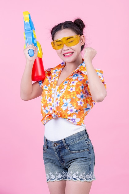 Happy girl holding a pink background water gun. Free Photo
