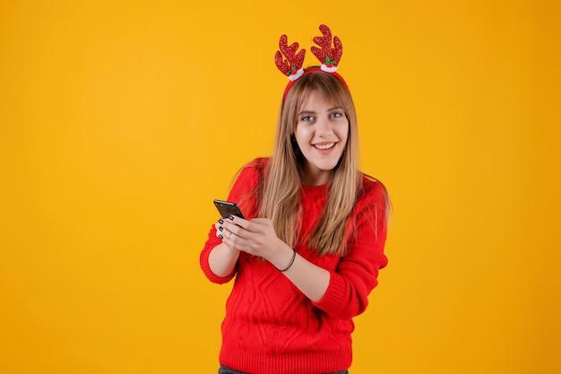 Happy girl holding smartphone in hands wearing funny christmas hoop Premium Photo
