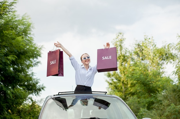 車のハッチ、割引とショッピングの概念でショッピングパッケージを保持している幸せな女の子 Premium写真