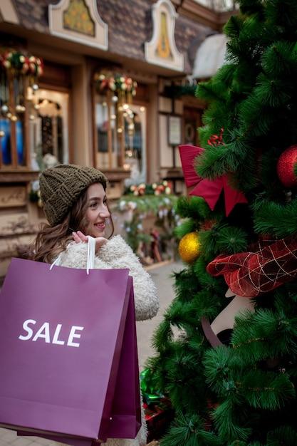 행복 한 소녀 크리스마스에 판매와 함께 상점에서 판매의 상징으로 Paperbags를 보유 프리미엄 사진
