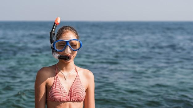 Счастливая девушка в маске и трубке на пляже Premium Фотографии