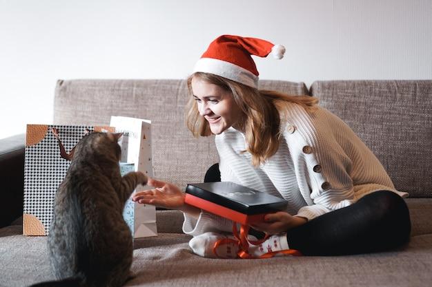 Счастливая девушка в новогодней подарочной коробке открытия шляпы санта-клауса и играя с кошкой. Premium Фотографии