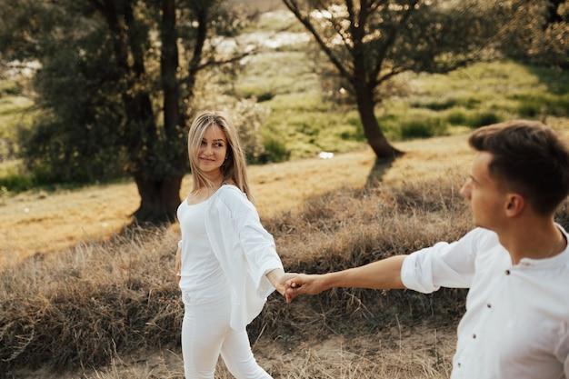 公園で手で男を保持している白い服を着た幸せな女の子。フォローしてください。 Premium写真