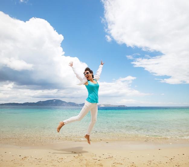 Happy girl jumping on the beach Premium Photo