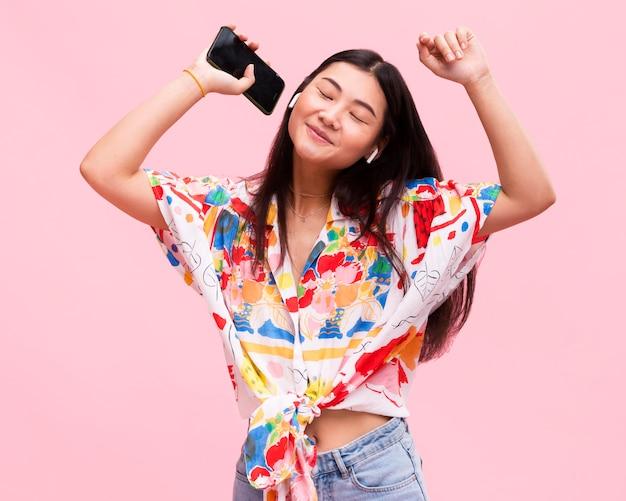 スマートフォンで音楽を聴いて幸せな女の子 Premium写真