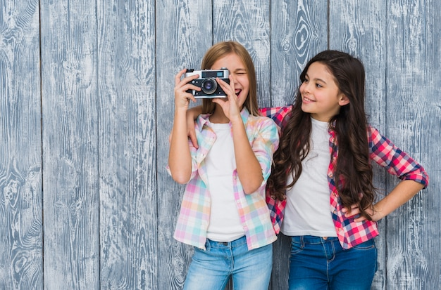 Happy girl looking at her friend looking through vintage camera standing against wooden wall Free Photo