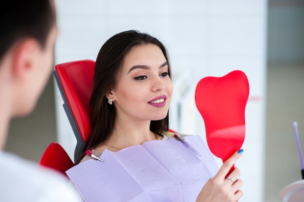 Happy girl looking in the mirror at a smile in the dentistry. Premium Photo