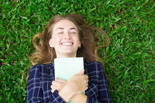 Happy girl lying on grass and embracing book Free Photo