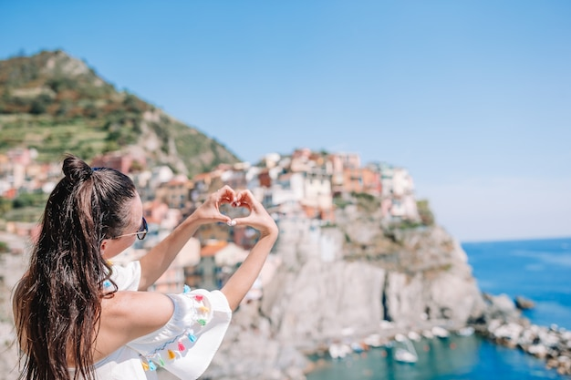 Happy girl making with hands heart shape on the old coastal village in cinque terre national park. Premium Photo