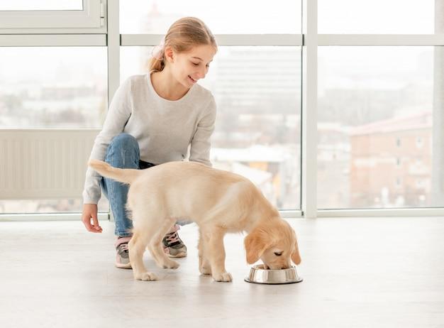Счастливая девушка рядом с едят щенка Premium Фотографии