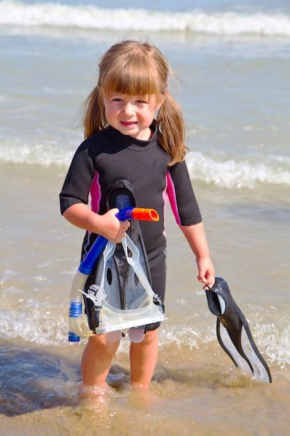 Счастливая девушка на пляже с красочными масками для лица и трубками, Premium Фотографии