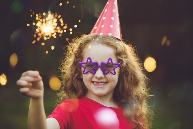 Happy girl in party hat with burning sparkler. Premium Photo