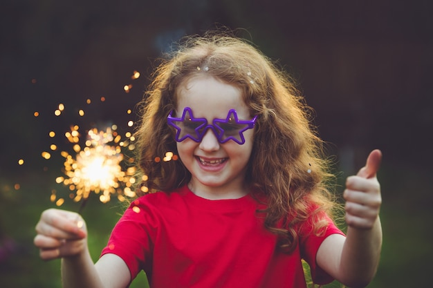 Happy girl in party with burning sparkler in her hand. Premium Photo