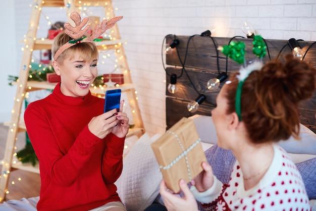 Счастливая девушка фотографирует самодельные рождественские подарки Бесплатные Фотографии