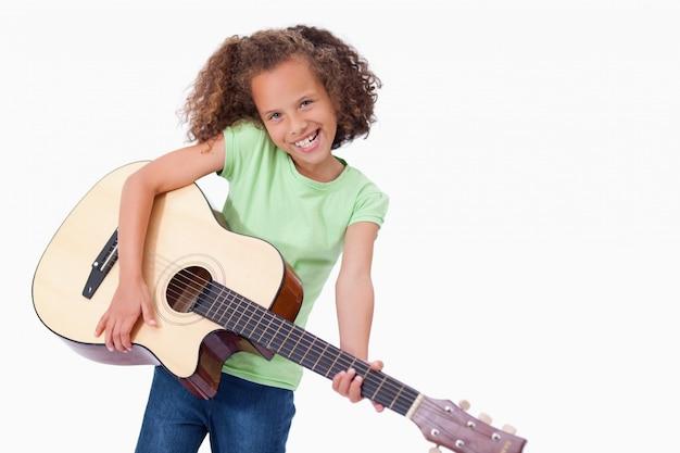 Happy girl playing the guitar Premium Photo
