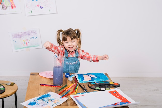 Happy girl putting paint brush into muddy water Free Photo