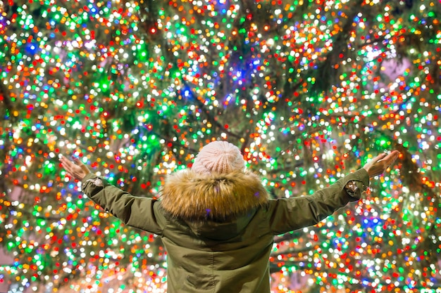 Happy girl on the rockefeller christmas tree in new york Premium Photo