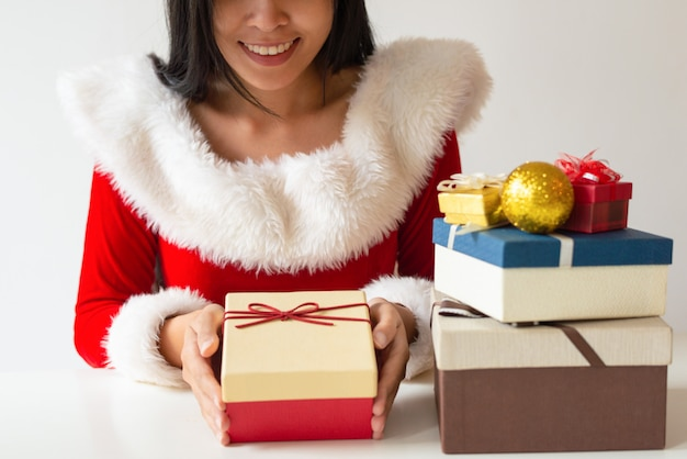 Happy girl in santa costume decorating christmas gifts Free Photo
