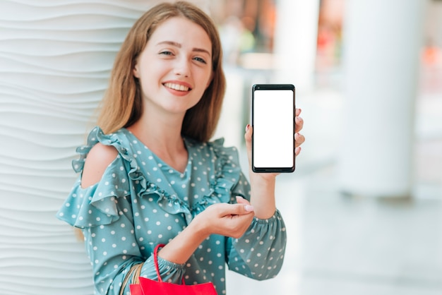 Happy girl showing her phone Free Photo
