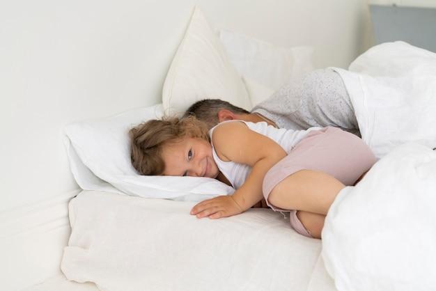 彼女の父親と一緒にベッドに座っている幸せな女の子 無料写真