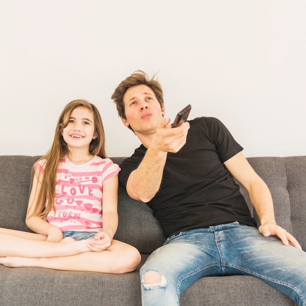 Happy girl sitting on sofa with her father holding remote control in hand Free Photo