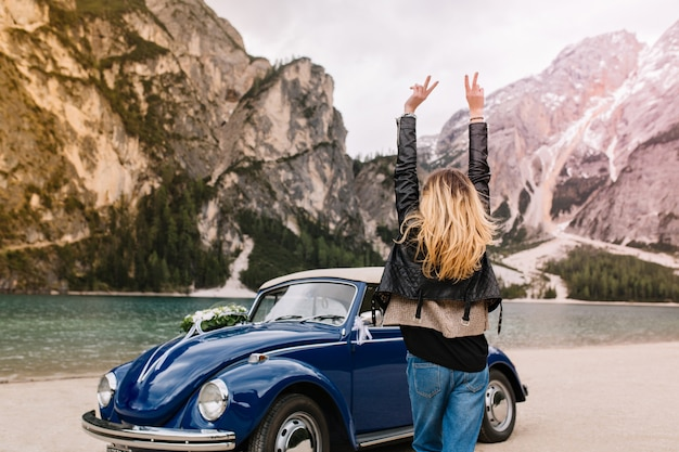 Happy girl in stylish attire having fun in italy looking at mountains and funny dancing with hands up Free Photo