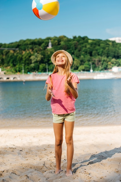 Happy girl throwing wind ball Free Photo