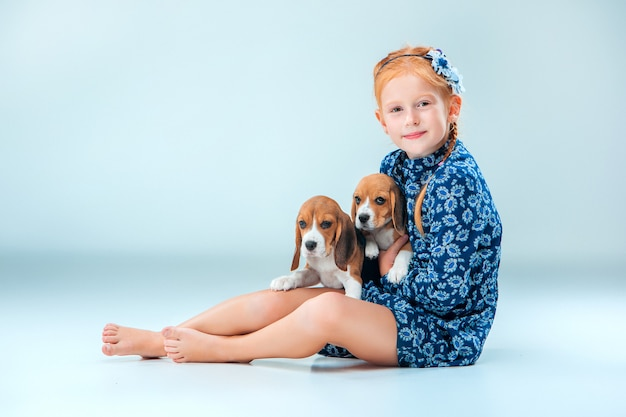 The happy girl and two beagle puppys Free Photo