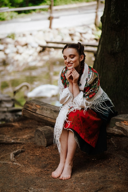 Happy girl in a ukrainian embroidered dress sitting on the bench Free Photo