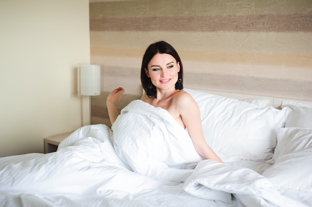 Happy girl waking up stretching arms on the bed in the morning. Premium Photo
