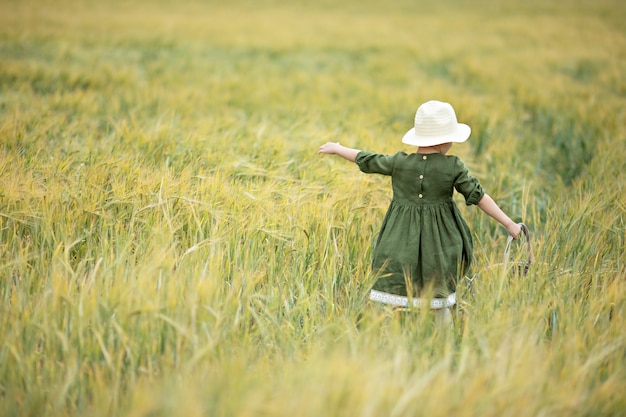 Happy girl walking in golden wheat, enjoying the life in the field. nature beauty and field of wheat. family outdoor lifestyle. freedom concept. cute little girl in summer field Premium Photo